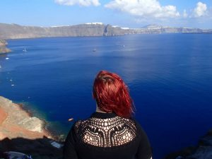 blogger with red hair looks out at the santorini caldera